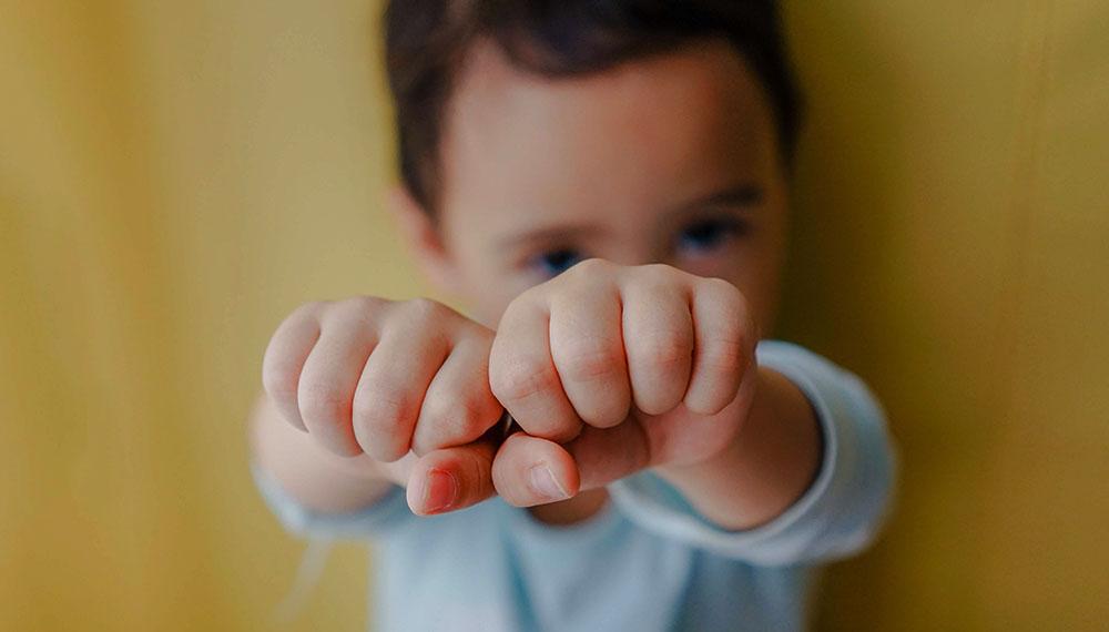 un enfant qui frappe avec ses deux mains