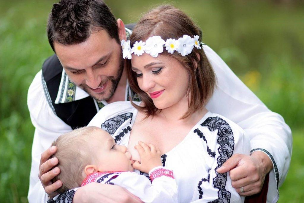 Un couple avec son bébé qui allaite dans les bras de sa maman