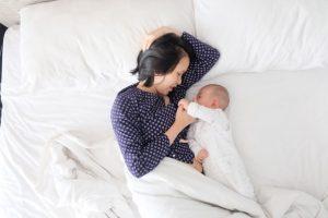 un bébé et sa maman sur un lit