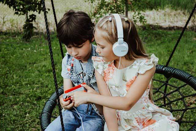 deux enfants sur une balançoire nid d'oiseau qui écoute de la musique